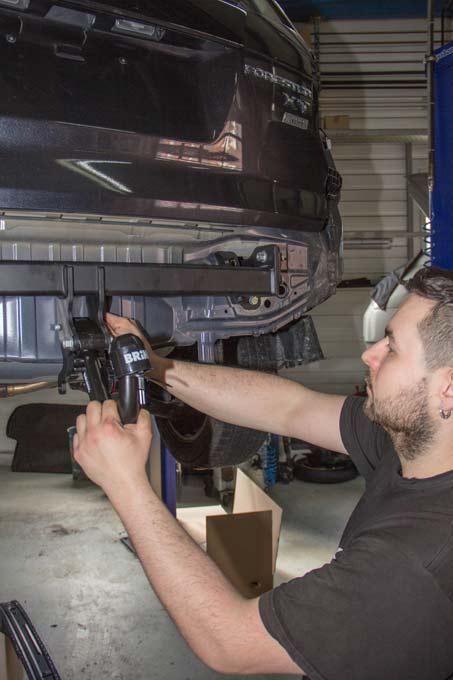 Der Mechaniker montiert eine Anhängerkupplung an ein neues Fahrzeug