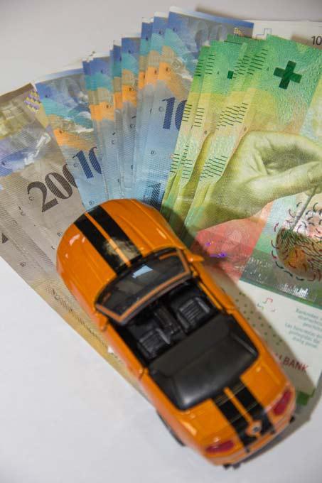Modellauto steht auf Banknoten