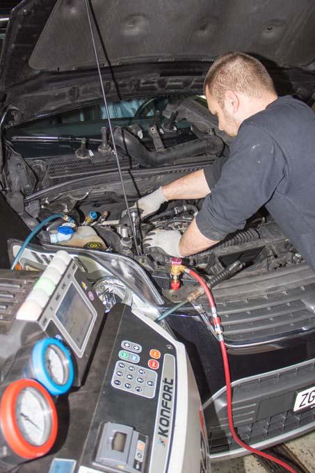 Das Klimawartungsgerät ist an das Fahrzeug angeschlossen und der Vorgang wird vom Mechaniker überwacht