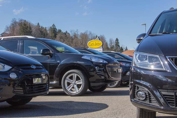 Sicht auf eine Reihe Occasionsfahrzeuge mit Firmentafel im Hintergrund